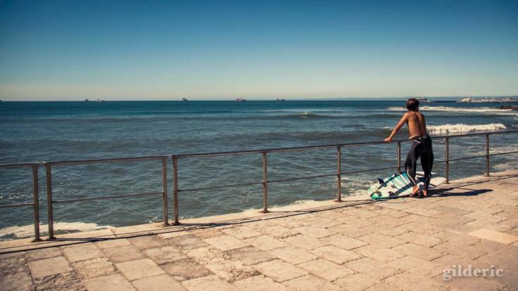 Jeune surfer rêvant devant l'océan (Cascais, Portugal)