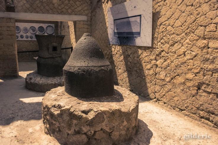 Meules en pierre dans la cour de la boulangerie à Herculanum