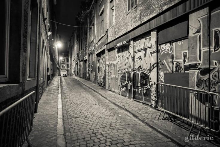 Couvre-feu à Liège : ruelle et graffitis dans la nuit.